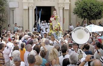 Le cortège se forme derrière la statue du saint à la sortie de l'église. La procession vers le port peut commencer.